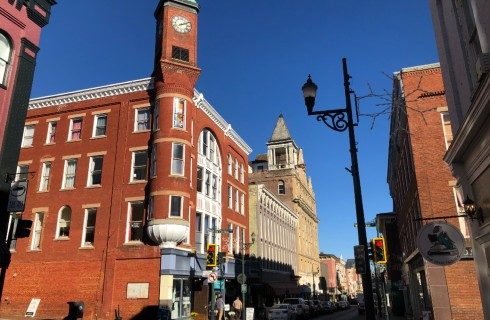 Downtown street corner with tall red brick buildings against a clear blue sky