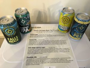 Four cans of beer from Seven Arrows Brewing Company around a list of beers with descriptions of each.