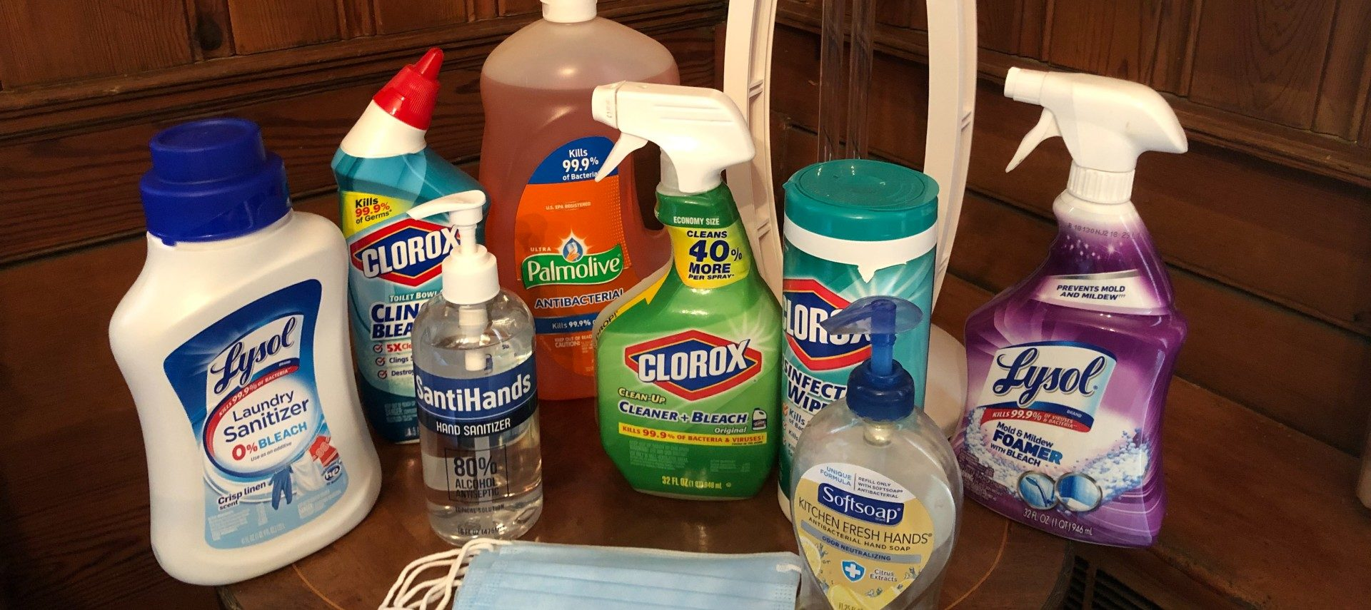 A variety of cleaning products, hand soap and face masks on a brown table