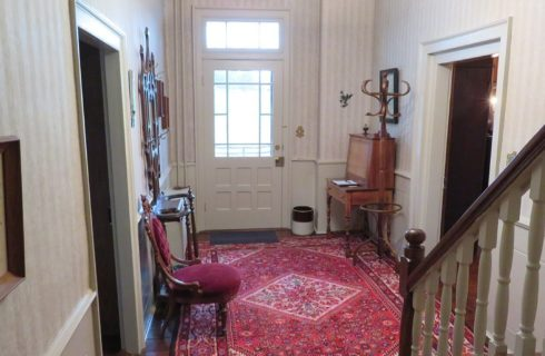 Front foyer of an elegant home showing white walls, red oriental rug and staircase leading upstairs