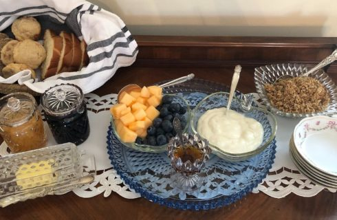 Wood buffet table holding an assortment of dishes for a yogurt, fruit and granola breakfast