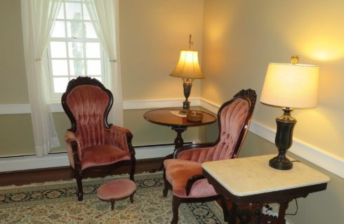 Sitting area in the corner of a room with two antique upholstered chairs and two side tables with lamps