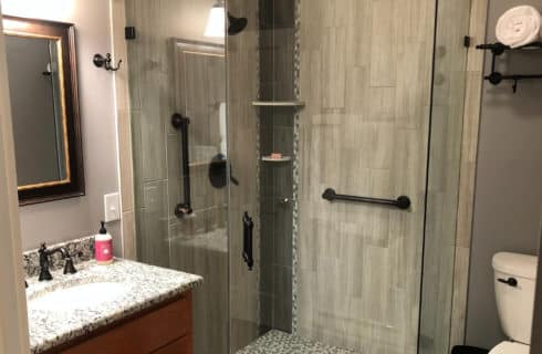 Beautiful tiled stand up shower with glass doors next to a granite sink vanity