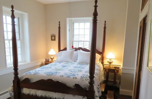 Beautiful queen four-poster bed in white and blue quilt in bright bedroom with large windows