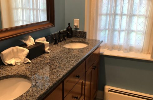 Bathroom with two sink vanity with granite countertop, large framed mirror and one window