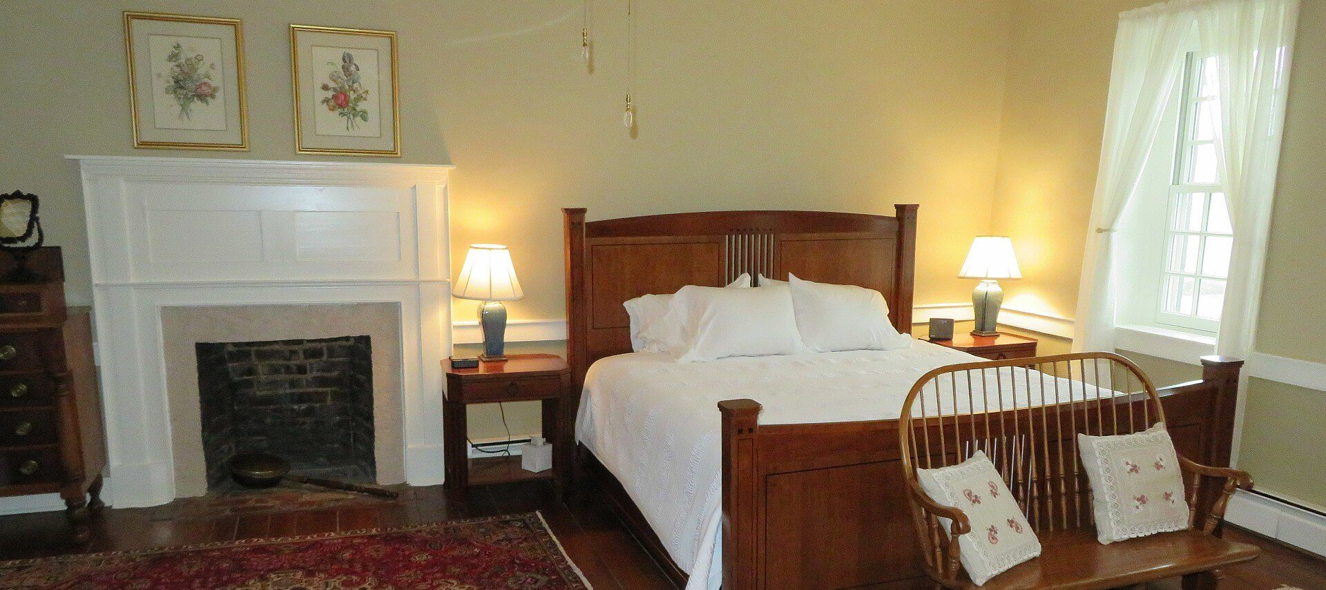 King bed with white linens in bedroom with bright windows and large fireplace with white mantle