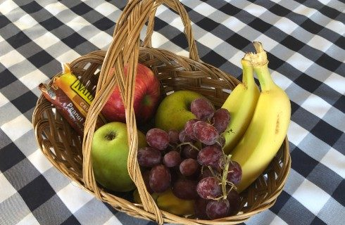 Brown wicker basket full of grapes, bananas, and apples on top a black and white checkerboard tablecloth