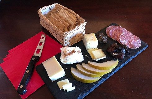 Black plate with sliced fruit, meats and cheeses next to a basket of crackers and red napkins
