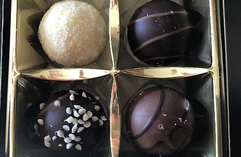 Box of four round chocolates, each a different flavor and color