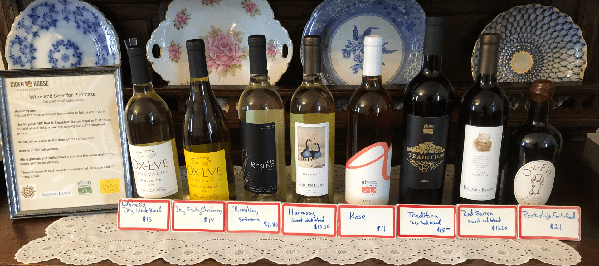 Eight bottles of wine on a breakfront with labels in front of each with pricing and description.